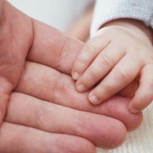 Vauvan käsi aikuisen kädessä.
