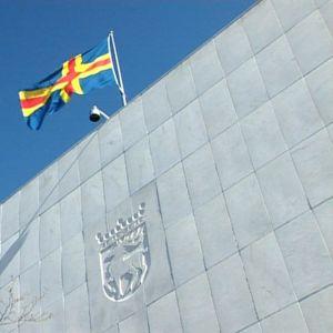 Ahvenanmaan lippu liehuu sinistä taivasta vasten. Seinällä Ahvenanmaan vaakuna.