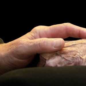 miehen käsi pitää vanhuksen kädestä kiinni