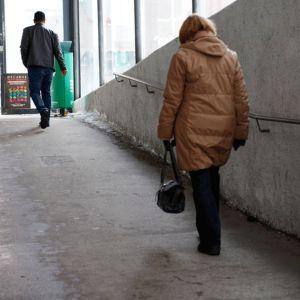 Nainen kävelee kävelytunnelissa.