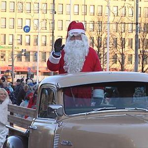 Joulupukki vilkuttaa auton lavalta yleisölle paraatissa.
