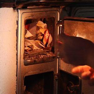 Nainen sytyttää tulta puuhellaan.