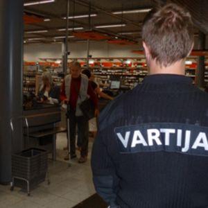 Vartija kauppakeskuksessa. Taustalla Alkon myymälä.