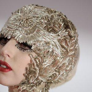 Lähikuva Lady Gagan kasvoista, tähdellä päässään kullanvärinen tiukka pääasuste.