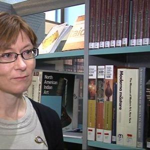 Rebekka Pilppulla kirjastohyllyjen keskellä