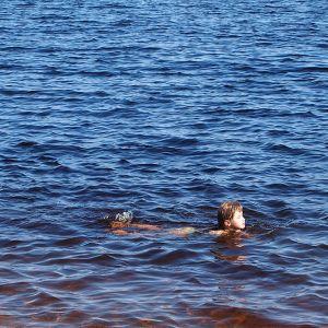 Tyttö ui rantavedessä.