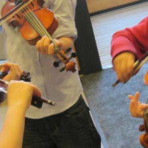Kolme nuorta soittajaa soittaa viulua.