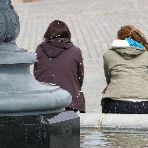 Kaksi tyttöä istuu suihkulähteen reunalla.