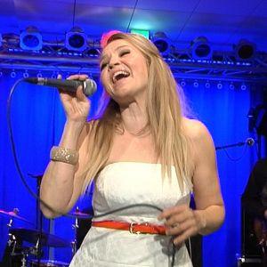 Marita Taavitsainen esiintymässä yhtyeensä kanssa Naapurivaaran Huvikeskuksessa.