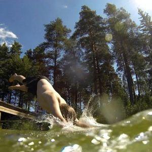 Lapsi hyppää järveen.