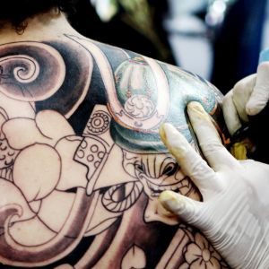 Miehelle tehdään tatuointia selkään.