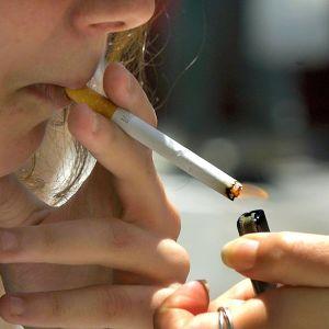 Toinen nainen sytyttää kreikkalaisen naisen savukkeen.