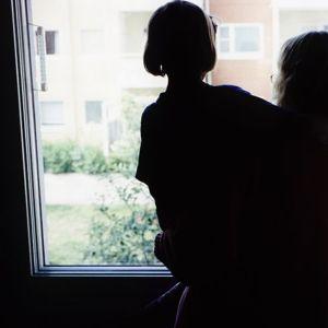 Nainen lapsi sylissään ikkunan ääressä.
