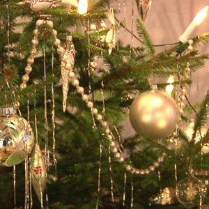 Kultaisilla koristeilla koristeltu joulukuusi.
