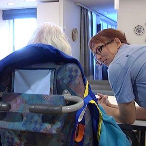 Hoitaja juttelee vanhuksen kanssa Porvoon Johanna-kodissa.