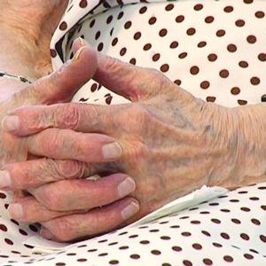 Vanhus istuu kädet sylissään.