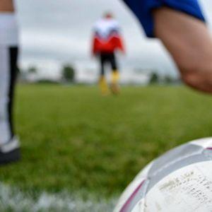 Jalkapalloilija venyttelee kentällä