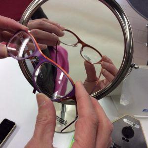 Optikko pitelee punaisia silmälaseja kädessään suurentavan peilin edessä.
