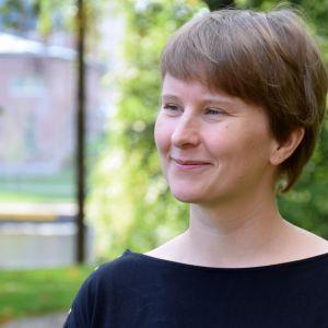 Elina Snicker hymyillee puistossa