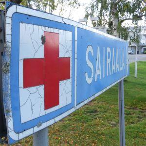 Kyltti, jossa punainen risti ja teksti sairaala.