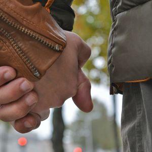 Nainen ja mies käsi kädessä.