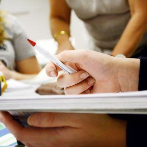 Opiskelijan kädet kirjalla