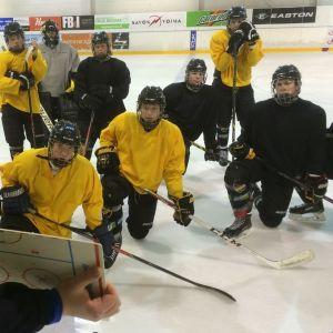 Nuoret jääkiekkoilijat kuuntelevat valmentajaa