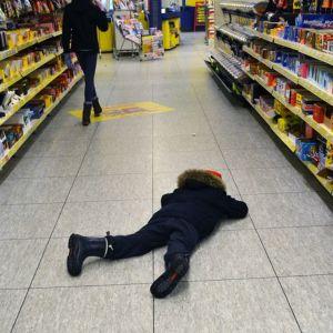 Lapsi murjottaa kaupassa karkkihyllyn edessä.