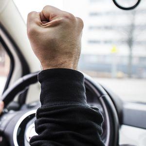 Henkilöauton kuljettaja näyttää nyrkkiä tiellä kulkevalle.