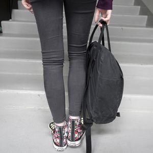 Nuori seisoo portaiden edustalla.