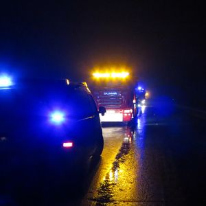 Hälytysajoneuvoja pimeällä tiellä
