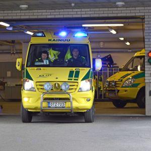 Ambulanssi lähtee sairaalan parkkihallista.