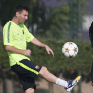 Leo Messi pomputtaa palloa ja Luis Enrique katselee.