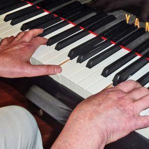 Kädet pianon koskettimilla.