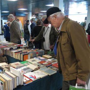Mies tutkivat antikvariaatin myyntipöytää.