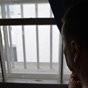 Vanki katselee kalteri-ikkunasta.