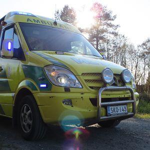 Ambulanssi parkissa hälytysvalot päällä.