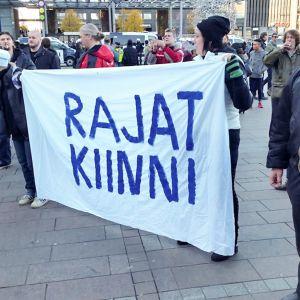 mielenosoittajat pitelevät banderollia