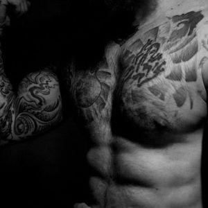 Tatuoitu mies poseeraa, kuvassa  näkyy hauista, vartalon yläosaa.