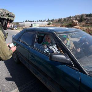 Israelilaissotilas tarkasti palestiinalaisten henkilöllisyystodistuksia Hebronissa lokakuussa 2015. Israelin armeija tiukensi alueen turvallisuustoimenpiteitä syksyn aikana lisääntyneiden väkivaltaisuuksien vuoksi.