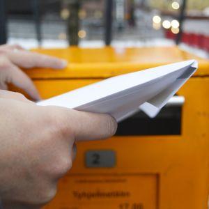 Ihminen työntää kirjekuorta postin laatikkoon.