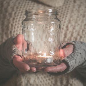 Kynttilä lasipurkissa.