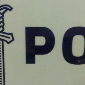 Sininen poliisin merkki ja osa poliisisanaa valkoisella pohjalla kyltissä.