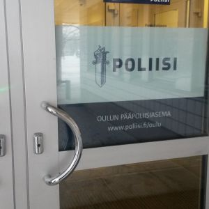 Oulun pääpoliisiaseman ulko-ovi, jossa poliisi-kyltti.