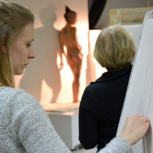 Nainen piirtää alastonmallia