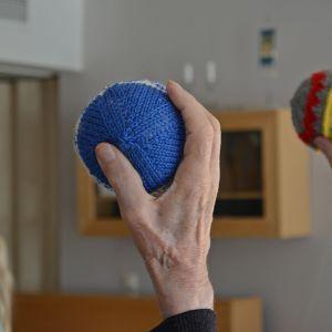 Vanhukset pitelevät neulottuja kuntopalloja ilmassa käsissään. Taustalla fysioterapeutti Hanna Väisänen näyttää mallia.