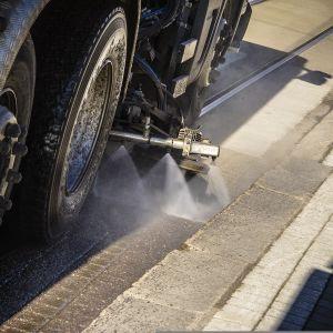 Huoltoauto puhdistaa raitiovaunuraiteita hiekasta ja katupölystä Mannerheimintiellä Helsingissä.