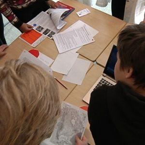 Joukko lukiolaisia ja yläkoululaisia pöydän ympärillä pohtimassa ongelmanratkaisutehtävää.