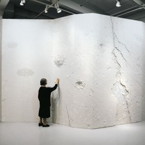 Rut Bryk seisoo teoksensa Jäävirta edessä.