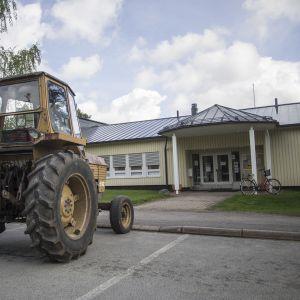 Traktori rakennuksen edessä parkissa.